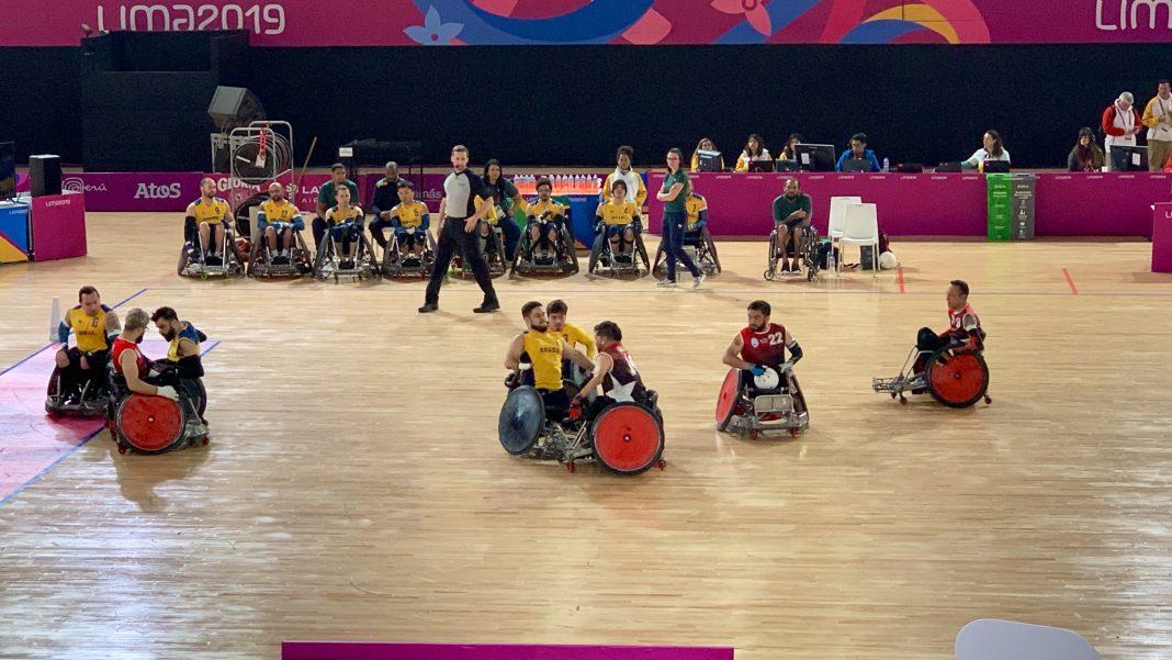 Em uma quadra ampla, jogadores de rugby em cadeira de rodas se chocam, tentando pegar a bola.
